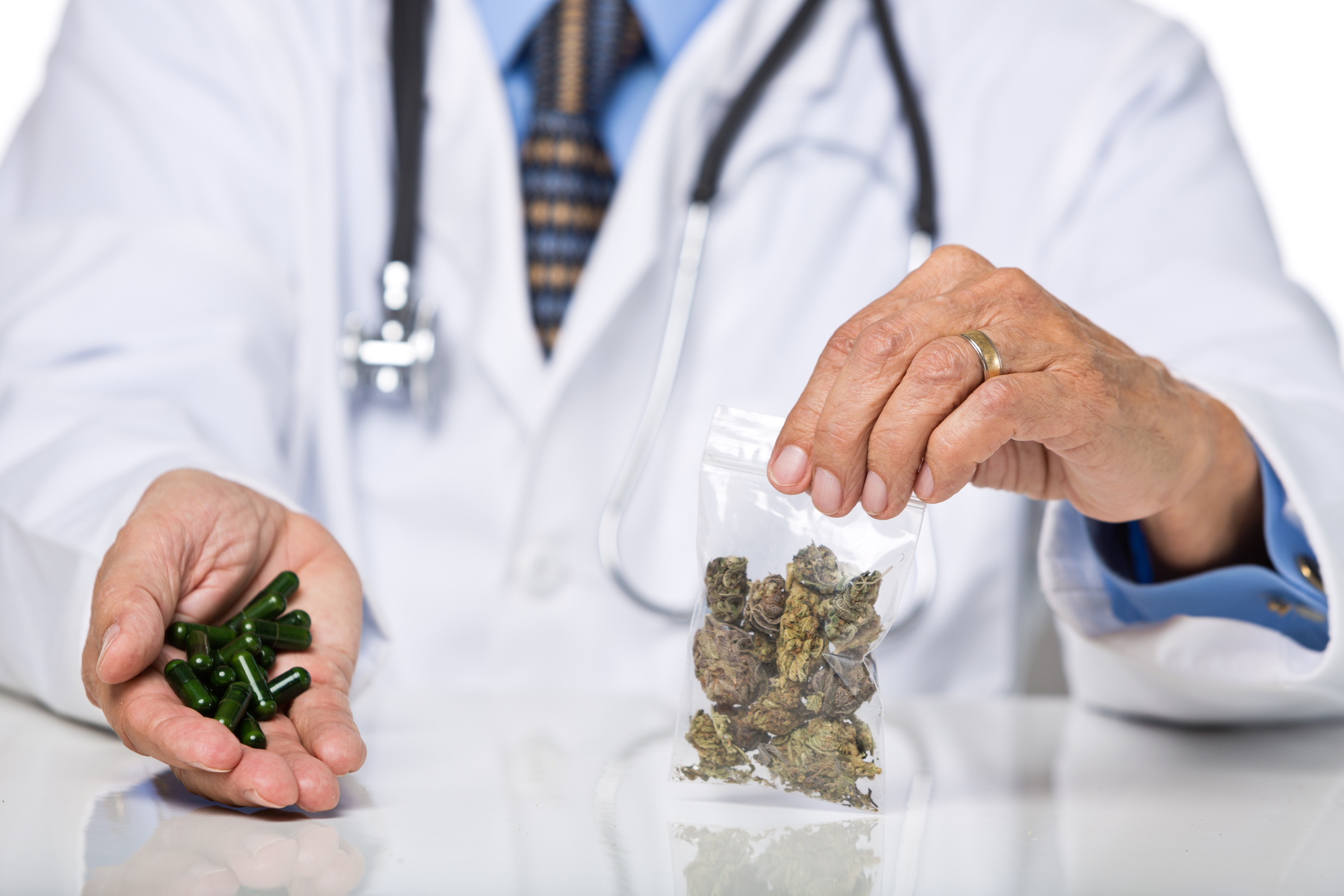 A physician holding a baggie of dried cannabis buds in his right hand, and cannabis oil capsules in his left hand.